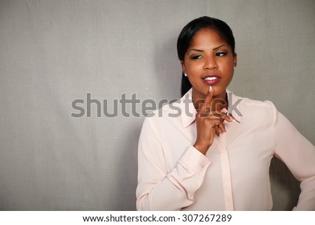 Charismatic woman in formal clothing thinking with hand on chin against grey background