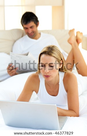 Charismatic woman using a laptop lying on bed at home
