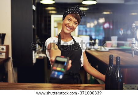 Charismatic young female small business owner requesting payment form a client holding out a handheld banking machine to process their credit card, focus to her face and warm friendly smile - stock photo