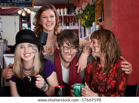 Charismatic young hipster with three female friends at a cafe - stock photo