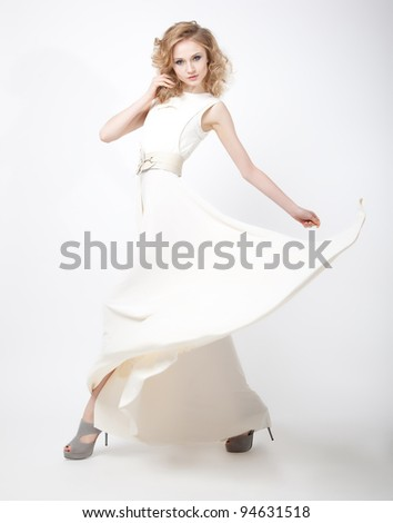 Charismatic young lovely female blond hair with flying vernal dress isolated over white background - stock photo