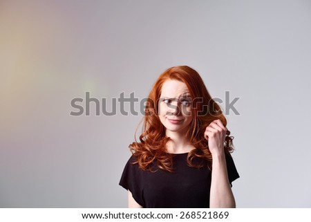 Charismatic young woman looking at the state of her long wavy red hair with a fun whimsical expression as she holds up a strand in her hand, over grey with copyspace - stock photo