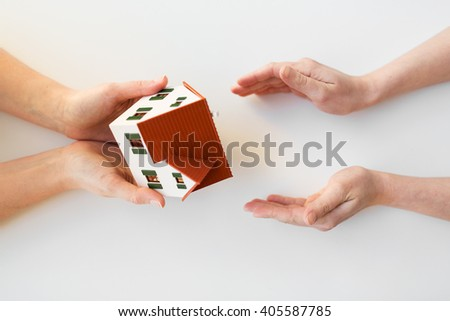 charity, building, sale, real estate and property concept - close up of hands giving and receiving house or home model - stock photo