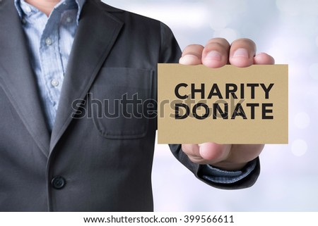 CHARITY DONATE Give Concept Businessman message on the card shown on blurred city background,