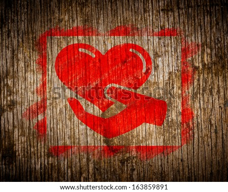Charity. Red Icon of Heart in the Hand Painted by Stencil on Wood. Grunge Background. - stock photo