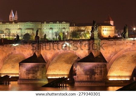Charles bridge across Vltava river with the Prague castle in the background at night, Czech Republic - stock photo