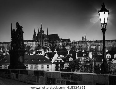 Charles Bridge at sunrise, Prague, Czech Republic. Dramatic statue and view on Prague Castle with St. Vitus Cathedral. Black and white - stock photo