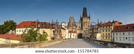 Charles Bridge (1357) bathed in warm early morning sunlight leading to Little Quarter Tower and St Vitus Cathedral (1714) in the magical city of Prague. - stock photo