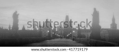 Charles Bridge in fog at sunrise, Prague, Czech Republic. Dramatic statues and medieval towers. Unique panoramic view at dawn when there are almost no people on the bridge. - stock photo