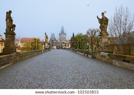 Charles Bridge in Prague on a spring foggy morning. - stock photo