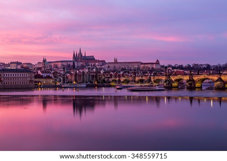 Charles Bridge in Prague, towards the Lesser Quarter and Prague Castle at sunset with a colorful vibrant sky.  - stock photo