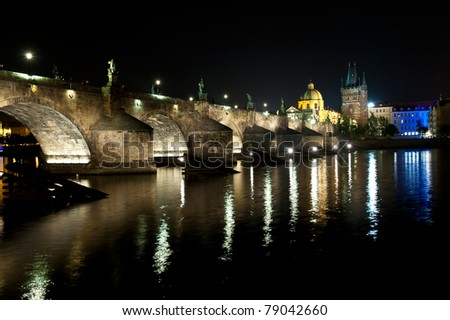 Charles bridge in Prague with lantern lights is reflecting in the river Vltava