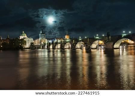 Charles Bridge reflected in Vltava river at night in Prague  - stock photo