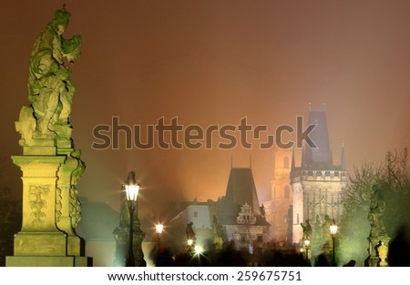 Charles bridge with tourists walking between rows of ghostly statues in foggy night, Prague, Czech Republic - stock photo