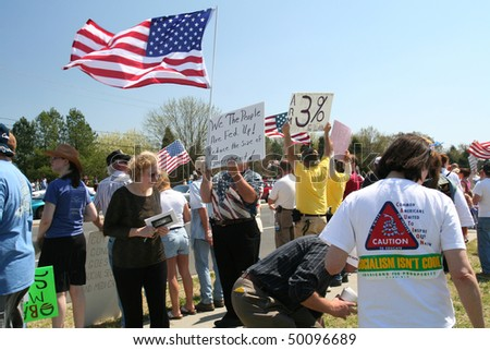 CHARLOTTE, NC - APRIL 2: Protesters on Good Friday. President Obama visits Charlotte NC to proclaim worst is over in the Economy. Citizens line the street in protest of government spending on April 2, 2010 in Charlotte, North Carolina - stock photo