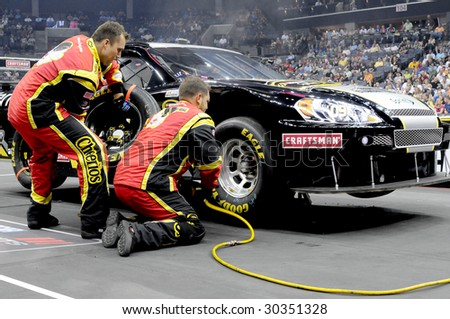 CHARLOTTE, NC MAY 14: Cheerios tire changer Clint Pitman removes the tire while carrier Shane Stevenson is ready in the NASCAR Pit Crew Challenge at Time Warner Cable Arena in Charlotte, NC May 14 2009 - stock photo