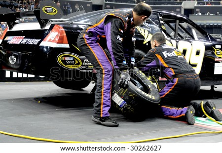 CHARLOTTE, NC MAY 14 2009 : Jonathan Sherman and Heath Cherry team up with rear tire duties in the NASCAR Pit Crew Challenge at Time Warner Cable Arena in Charlotte, NC May 14 2009 - stock photo