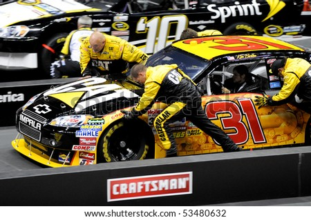 CHARLOTTE, NC - MAY 19:  Kim Burton steers the number 31 CAT car while crew members push the car to a finish in the 2010 NASCAR Pit Crew Challenge  MAY 19 2010 in CHARLOTTE, NC - stock photo