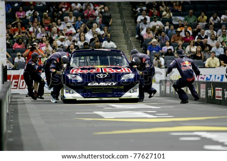 CHARLOTTE, NC MAY 19: The No. 4 Red Bull Racing pit Crew race to push the car over the finish line during the 2011 NASCAR Pit Crew Challenge at Time Warner Cable Arena in Charlotte, NC on May 19 2011 - stock photo