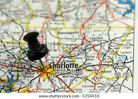 Charlotte, North Carolina. Push pin on an old map showing travel destination. - stock photo
