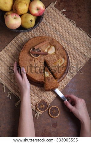 Charlotte with apples and cinnamon and fruit in a wattled basket