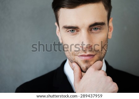 Charm and confidence. Thoughtful young man holding hand on chin and looking at camera while standing against grey background - stock photo
