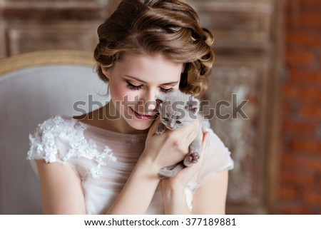 Charming and beautiful girl in white dress sitting on the couch on a background of a brick wall, smiling and holding his little kitten, close-up - stock photo