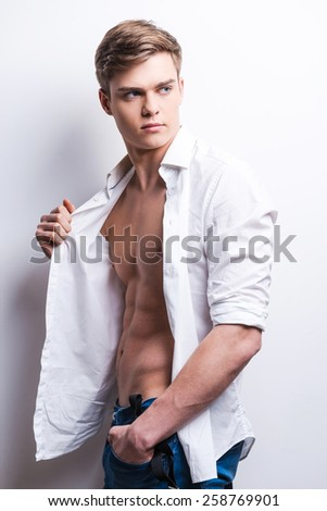 Charming and confident. Handsome young muscular man posing while standing against grey background - stock photo