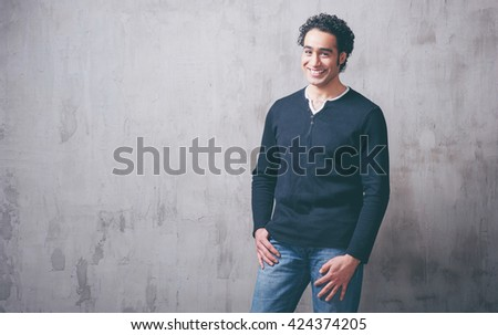 Charming and self-confident. Handsome young arabic man holding hand in pockets and looking at camera while standing against grey background - stock photo