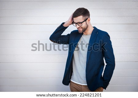 Charming and self-confident. Handsome young man in smart jacket adjusting his hair and smiling while standing in front of the brick wall - stock photo
