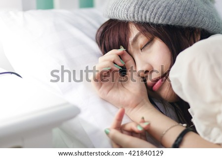 Charming Asian girl wearing pajamas on the bed - stock photo