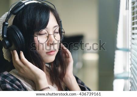 Charming Asian girl with earphones - stock photo