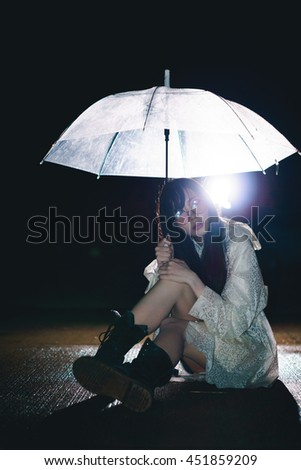 Charming Asian girl  with umbrella and raincoat at night