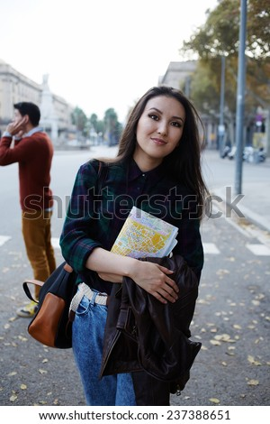 Charming asian tourist girl holding city map standing on big beautiful road, stylish hipster girl standing with city map on beautiful road covered with autumn leaves - stock photo