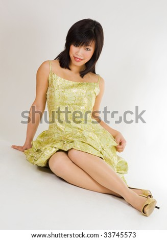 Charming asian woman smiling woman sitting in gold evening dress smiling - stock photo