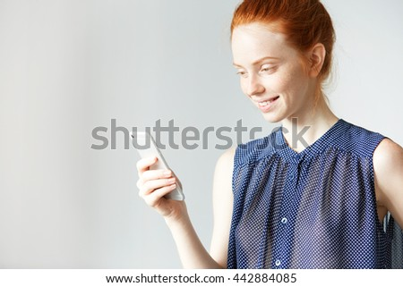 Charming attractive white student girl wearing blue stylish spotted dress skyping with her friend using mobile phone, smiling, looking happy and shy, having healthy freckled skin and tender smile - stock photo