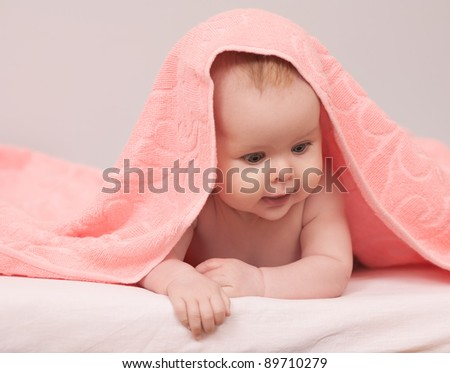 Charming baby. Beautiful baby under pink towel - stock photo