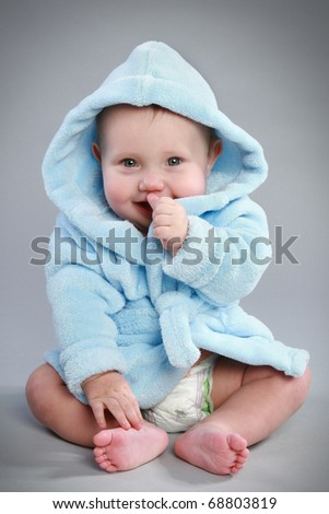 Charming baby boy in a blue bathrobe with a hood - stock photo
