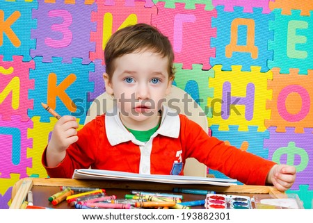 Charming baby draws a pencil in the album