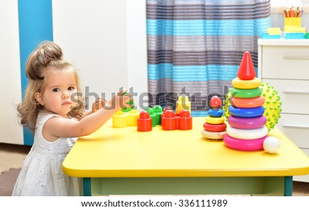 Charming baby girl playing with toys. Indoors. Room  interior.