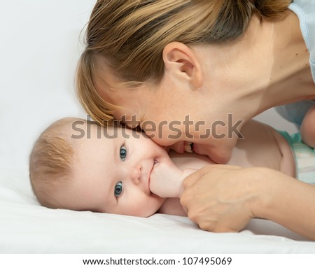 Charming baby with mother. Woman kisses her blue eyed baby - stock photo