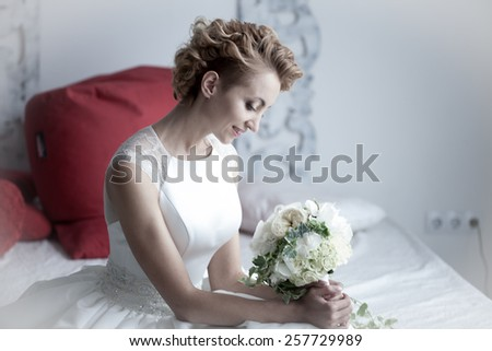 charming beautiful bride holding wedding bouquet in her hands. bride in white dress in a luxury interior lying on the beautiful white bed  - stock photo