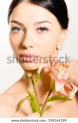 charming beautiful young brunette woman with perfect skin, blue eyes and luxury jewelry earring holding lily flower & looking at camera isolated on white background close up portrait picture - stock photo