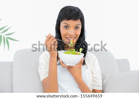 Charming black haired woman in white clothes eating salad in a living room - stock photo