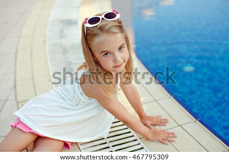 Charming blond girl in pink shorts sitting around the pool in the summer
