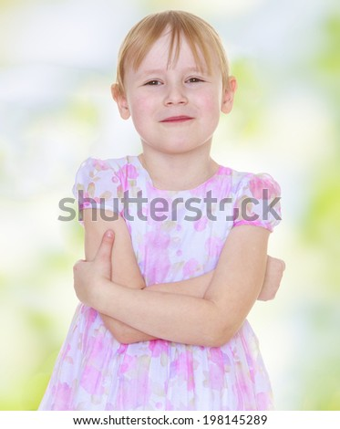 Charming blonde girl in a dress with pink flowers standing on a blurred the background of the green summer