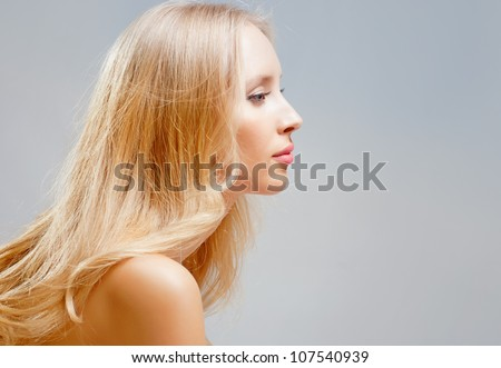 Charming blonde girl's face in the profile - stock photo