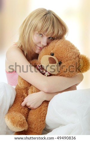 Charming blonde in bed embraces teddy bear - stock photo