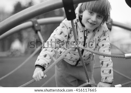 Charming Boy with toothless smile climbing ropes - stock photo