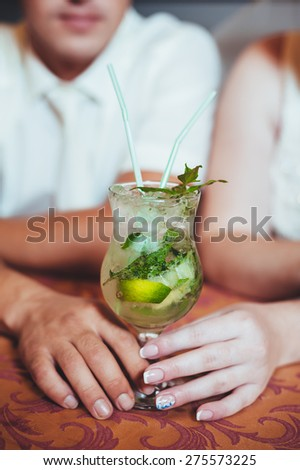Charming bride and groom drink a mojito on their wedding celebration in a luxurious restaurant